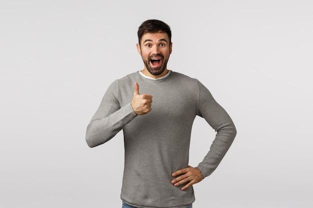 Geweldig idee, laten we het doen. opgewonden, vrolijke, ondersteunende bebaarde volwassen man in grijze trui, geef positieve feedback, aanbid iets heel goeds, toon duim-omhoog goedkeuring, leuk of enthousiast gebaar