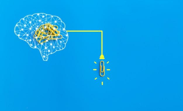 Geweldig ideeënconcept met menselijke hersenen, paperclip, het denken, creativiteit, gloeilamp op blauwe achtergrond, nieuw ideeënconcept