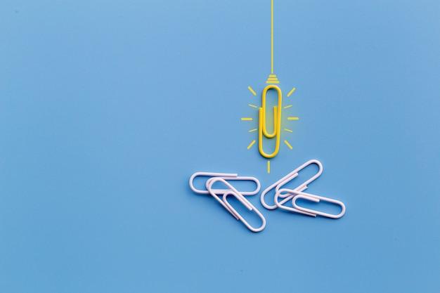 Geweldig ideeënconcept met paperclip, het denken, creativiteit, gloeilamp op blauwe achtergrond, nieuw ideeënconcept.