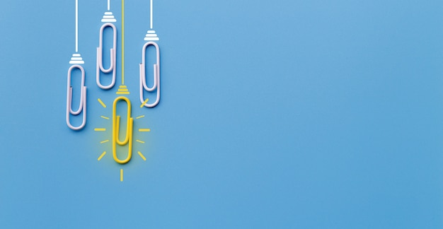 Geweldig ideeënconcept met paperclip, het denken, creativiteit, gloeilamp op blauwe achtergrond.