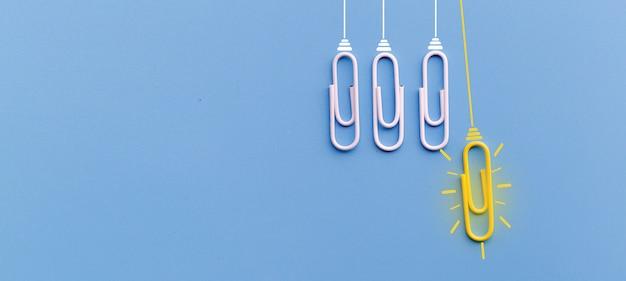 Geweldig ideeënconcept met paperclip het denken creativiteit gloeilamp op blauwe achtergrond