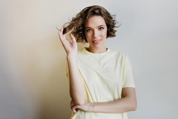 Geweldig kaukasisch meisje in goed humeur spelen met haar korte haar. verfijnd wit vrouwelijk model poseren met geïnteresseerde gezichtsuitdrukking.