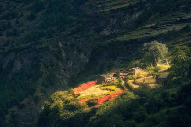 Geweldig klein dorp op de heuvel verlicht door een zonnestraal bij zonsopgang