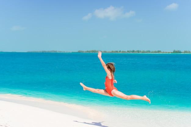 Geweldig klein meisje op het strand met veel plezier op zomervakantie