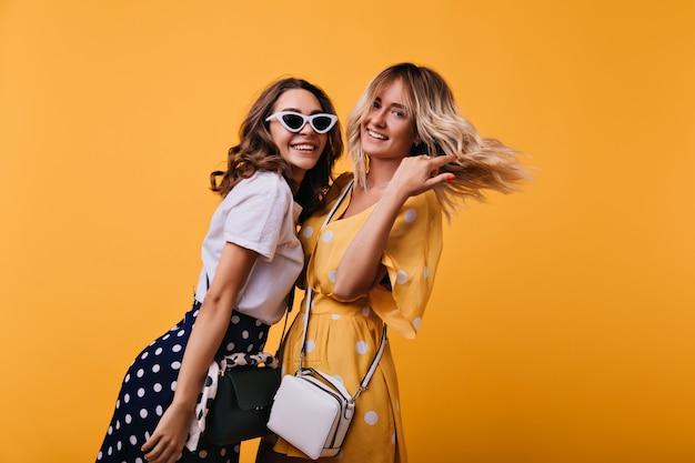 Geweldig krullend meisje in witte zonnebril met plezier met beste vriend. geïnspireerde zusters in trendy kleding die zich voordeed op oranje.