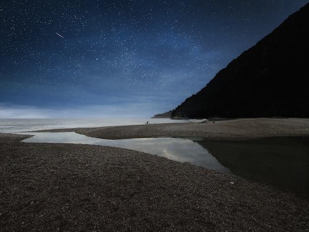 Geweldig landschap van berg in de buurt van de zee met stenen strand en blauwe sterrenhemel. olimpos strand, turkije.