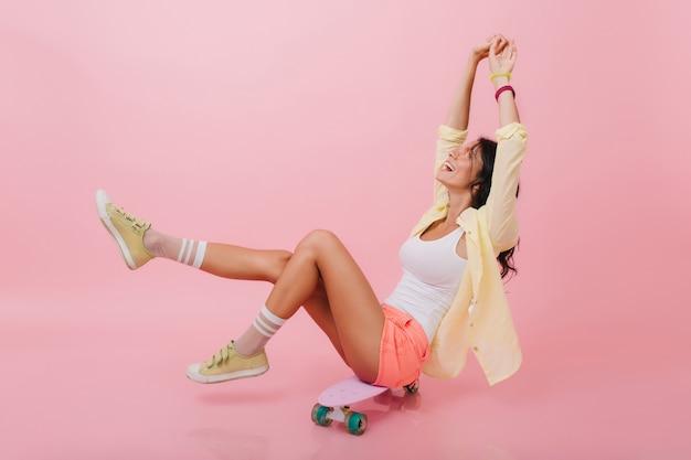 Geweldig latijns-meisje in roze gestreepte sokken genieten van het leven en glimlachen. sierlijke jonge vrouw met donker haar poseren met handen omhoog, zittend op een skateboard