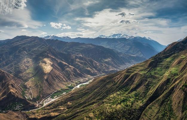 Geweldig lentelandschap met silhouetten van grote rotsachtige bergen
