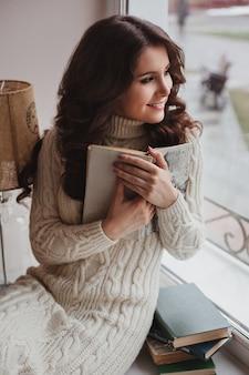 Geweldig meisje dat thuis een boek leest. een vrouw zit op de vensterbank en drukt het boek tegen zichzelf, dromerig kijkend uit het raam, ruimte.