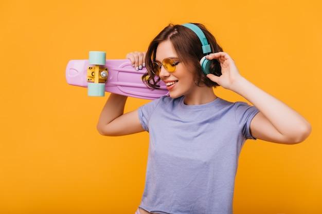 Geweldig meisje in blauwe koptelefoon dansen. binnen schot van enthousiaste jonge vrouw die met skateboard geluk uitdrukt.