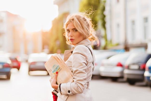 Geweldig meisje in trendy jas over schouder kijken terwijl poseren op straat met auto's op de achtergrond