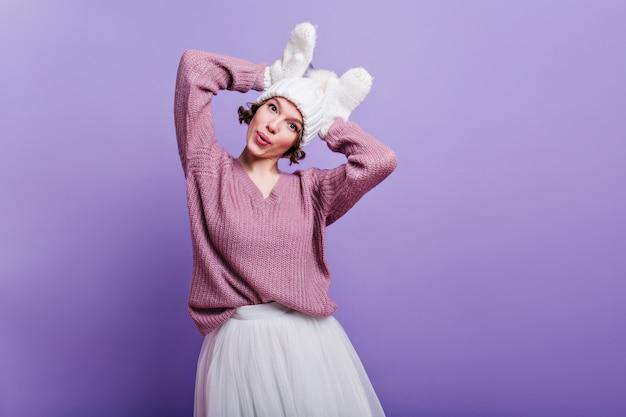Geweldig meisje in wollen handschoenen gek rond indoor foto van charmant vrouwelijk model in gebreide muts en witte rok grappige gezichten maken op paarse muur.