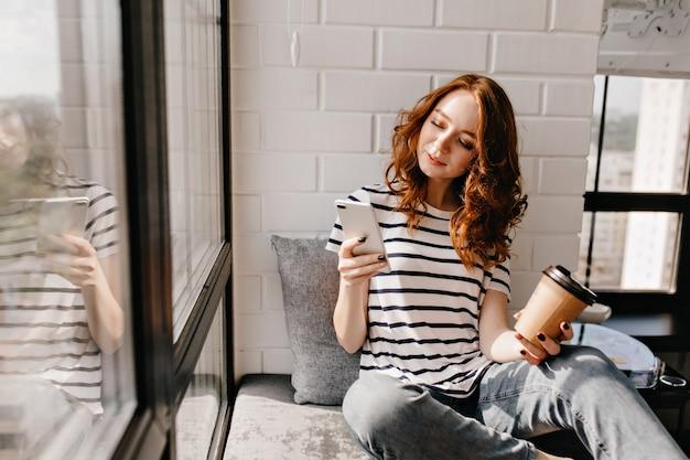 Geweldig meisje koffie drinken en sms-bericht. aantrekkelijk vrouwelijk model dat van latte geniet terwijl het telefoonscherm bekijkt.