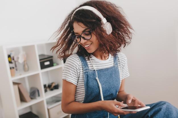 Geweldig meisje met donkerbruin krullend haar met plezier in kantoor luisteren muziek in witte oortelefoons