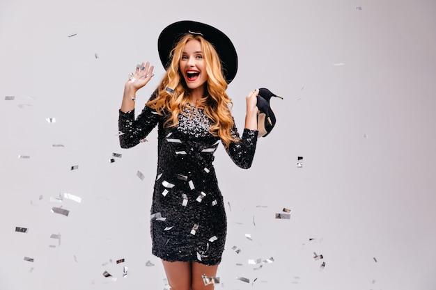 Geweldig meisje permanent onder confetti en haar schoenen vast te houden. indoor foto van geïnspireerde blonde vrouw in elegante hoed.
