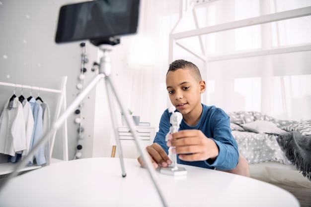 Geweldig model. doordachte afro-amerikaanse jongen blogger video-opname tijdens het aanraken van speelgoed