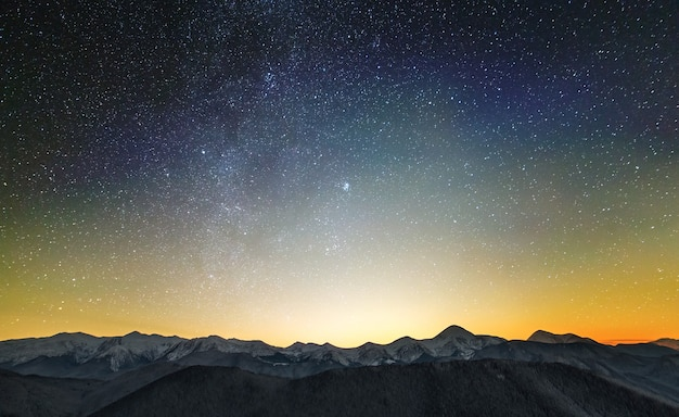 Geweldig nachtberglandschap met hoge toppen en heldere sterrenhemel hierboven.