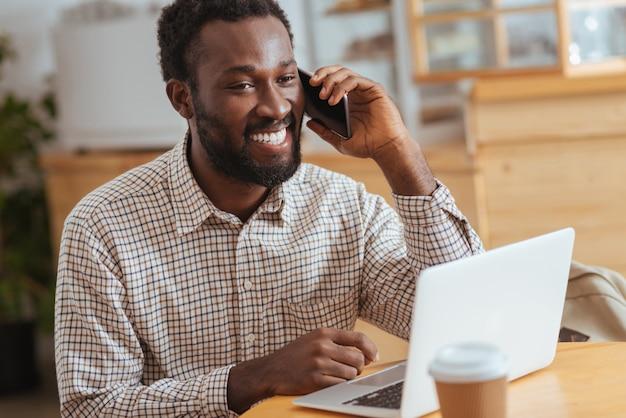 Geweldig nieuws. aangename gelukkige man zit aan de tafel in het café, werkt op de laptop en praat aan de telefoon terwijl hij breed lacht
