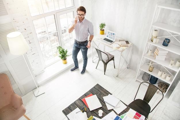 Geweldig nieuws. geïnspireerde jonge zakenman praten aan de telefoon en glimlachen