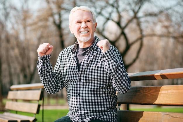Geweldig nieuws. jolly senior man rustend op de bank en stijgende handen