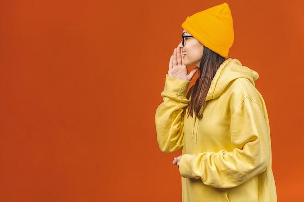 Geweldig nieuws! vrolijk gelukkig mooi meisje dat geheim op oranje achtergrond vertelt.