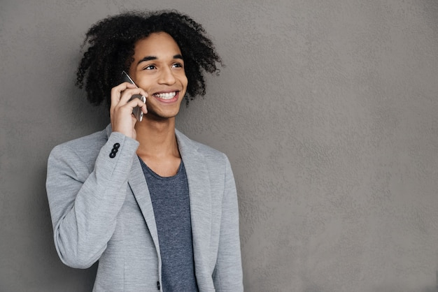 Geweldig nieuws. vrolijke jonge afrikaanse man die op mobiele telefoon praat en glimlacht terwijl hij tegen een grijze achtergrond staat