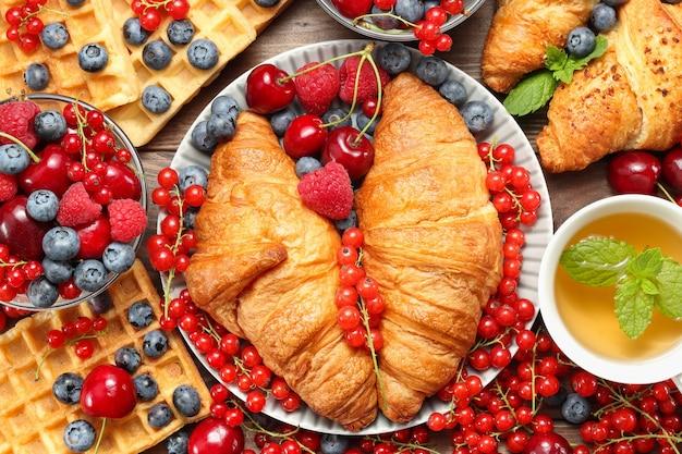 Geweldig ontbijt met heerlijke botercroissants met verschillende bessen en wafels kopje thee