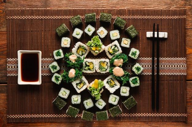 Geweldig ornament van vegetarische sushi-broodjes, geserveerd op een bruine stromat, plat gelegd. japanse traditionele keuken, voedselkunst, culinair meesterwerk.