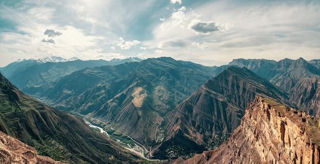 Geweldig panoramisch uitzicht van pas naar bergdal in zonlicht