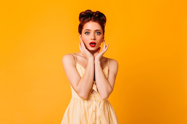 Geweldig pinup meisje poseren in schattige jurk. studio shot van knappe gembervrouw geïsoleerd op gele ruimte.