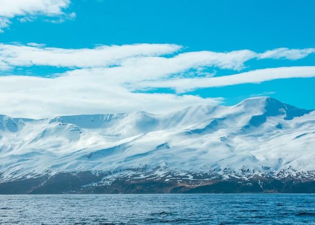 Geweldig schot van besneeuwde bergen en de zee
