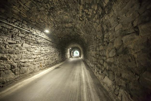 Geweldig schot van de ingang van een oude stenen tunnel vanaf het andere uiteinde van een oude stenen tunnel