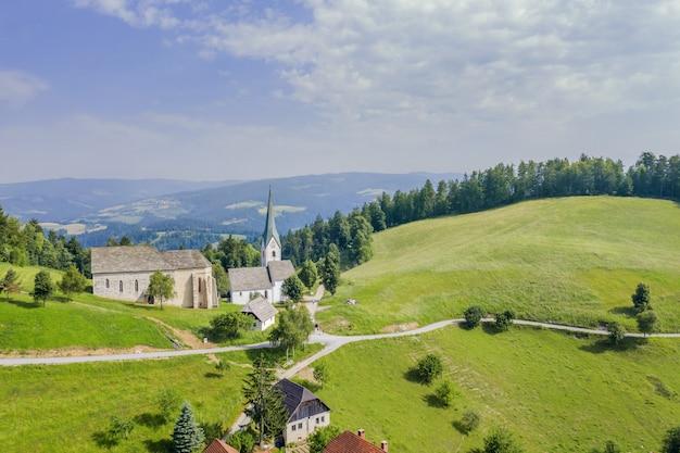 Geweldig shot van de lese kerk in slovenië in een vallei met een bewolkte hemel