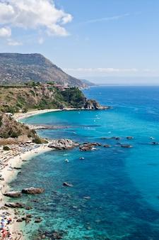 Geweldig tropisch panoramisch uitzicht op de turquoise golfbaai, zandstrand, groene bergen en planten