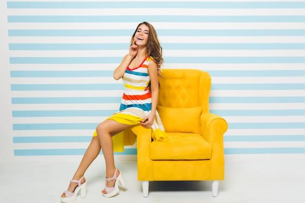 Geweldig vrolijk meisje met lange gebruinde benen zittend op gele fauteuil en haar gezicht met de hand aan te raken. portret van een prachtige jonge dame trendy sandalen en kleurrijke kleding dragen.