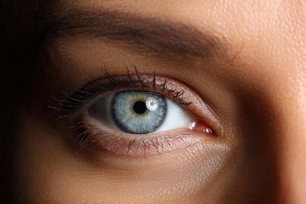 Geweldig vrouwelijk blauw en groen gekleurd wijd geopend oog in close-up met weinig licht