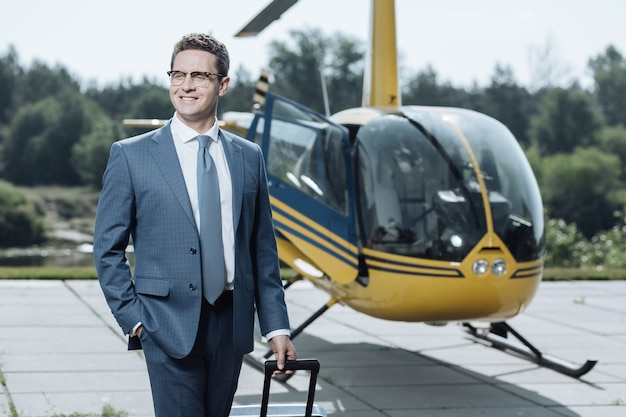 Geweldige aankoop. succesvolle jonge ceo puffend op zijn borst en trots op de aankoop van een helikopter, nadat hij een vlucht had genomen