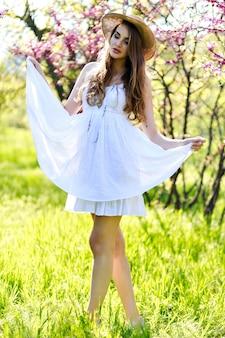 Geweldige aantrekkelijke jonge vrouw met lang haar, in hoed, witte lichte jurk genieten van zonnige lentedag in tuin op bloeiende sakura achtergrond.