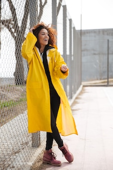 Geweldige afrikaanse krullende jonge dame met gele jas