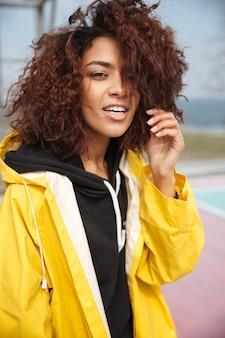 Geweldige afrikaanse krullende jonge vrouw, gekleed in gele jas