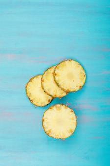 Geweldige ananasschijven op blauw. bovenaanzicht.