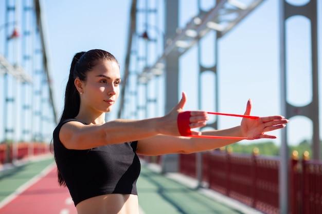 Geweldige atletische vrouw doet training met rubberen weerstandsband op een brug. ruimte voor tekst