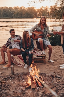 Geweldige avond. groep jongeren in vrijetijdskleding die lacht terwijl ze genieten van een strandfeest bij het kampvuur