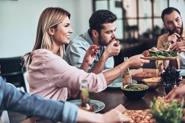 Geweldige avond met vrienden. groep jongeren in vrijetijdskleding die eet en glimlacht