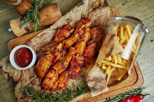 Geweldige biersnack - pittig gebakken buffelvleugels. bbq-vleugels met garnituur van frietjes op een houten dienblad. bovenaanzicht, plat eten. pub eten