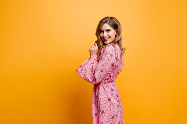 Geweldige blanke vrouw in lange jurk kijkt over de schouder. jocund krullend meisje in roze outfit poseren op gele muur.
