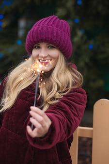 Geweldige blonde vrouw die plezier heeft met sprankelende bengaalse lichten op de nieuwjaarsspar in kiev