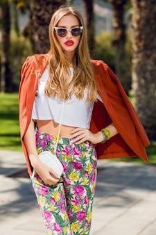 Geweldige blonde vrouw in trendy zomer outfit poseren buitenshuis