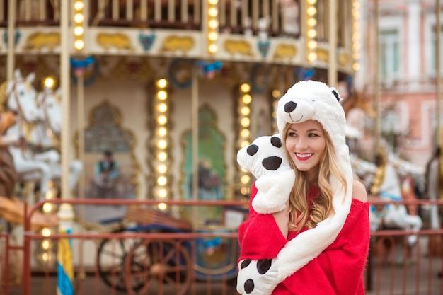 Geweldige blonde vrouw met een rode gebreide trui en een grappige hoed, poserend op de achtergrond van een carrousel met verlichting