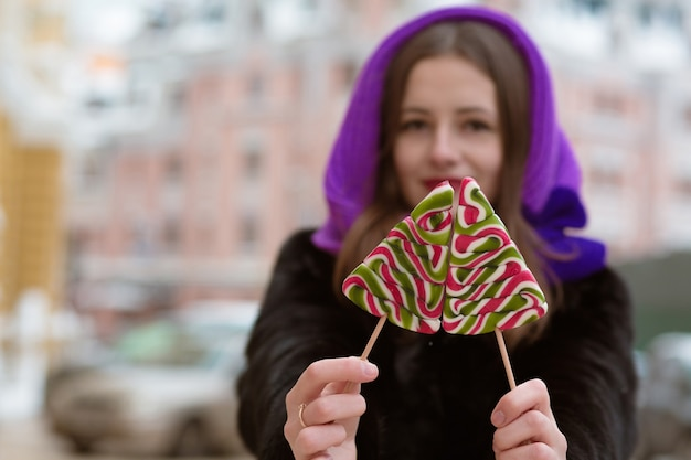 Geweldige brunette vrouw die winteroutfit draagt, met smakelijke karamelsnoepjes. achtergrond vervagen